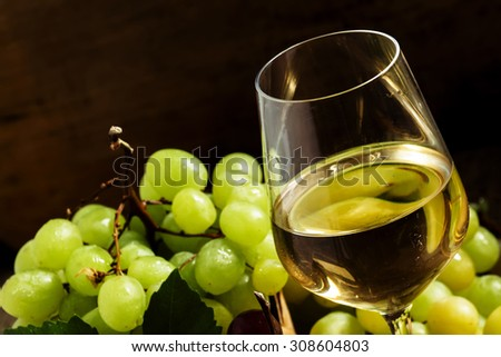 White wine in a glass and green and red grapes in a wicker basket, still life in a rustic style, toned image, selective focus