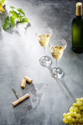 White wine in glasses, a bottle, grapes and grape leaves on the table. Bottle of white wine with label. Light background.