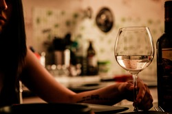 White wine into the wineglass and female hand.