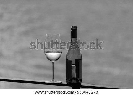 White wine on outside deck with bottle in black and white