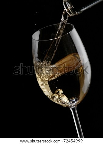 White wine pour in a glass on black background