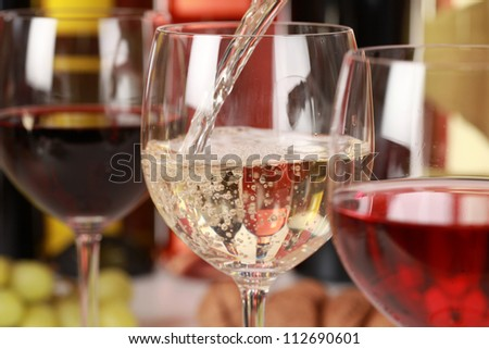 White wine pouring into a wine glass. Selective focus on the white wine.