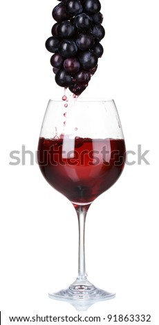 White wine pouring into glass and grapes isolated on white