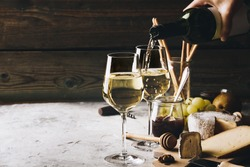 White wine pouring into glasses with charcuterie assortment on t