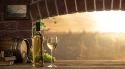 White wine tasting in the wine cellar: wineglass and bottles next to the window and panoramic view of vineyards at sunset