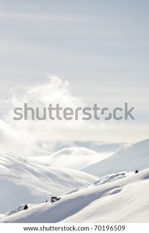 White winter mountains covered with snow in blue cloudy sky. Alps. France. Saint Jean d'Arves.