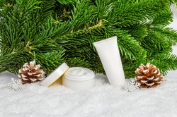White winter skin care cosmetic products in snow with Christmas tree and pine cones. Face cream jar and hand creme tube. Organic skin moisturizer, nourishing mask and body lotion mockup
