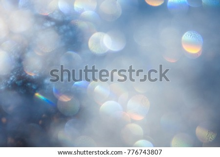 White winter sparkle bokeh with natural sunlight. Dots of light in a pretty pattern for background. Lens flare with rainbow spectrum captured in camera. Glittery, festive photo for the holiday season.
