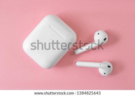 white wireless headphones on pink background. female headphones. copy space