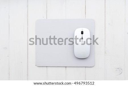 White wireless mouse on a mouse pad, top view #496793512