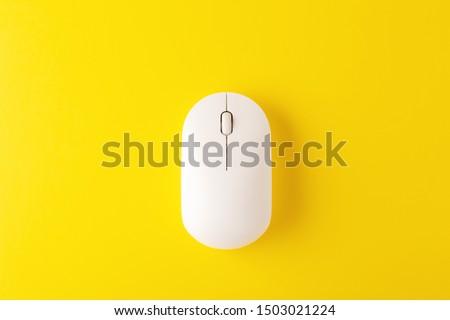 Photo of  White wireless mouse on yellow background, minimal, flatlay