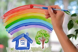 White woman drawing rainbow over house, garden on window at home. Hand of woman painting with brush rainbow on glass during coronavirus Covid-19 quarantine. Peace concept, societal friendship, harmony