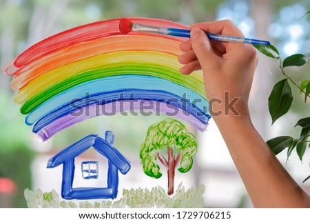 White woman drawing rainbow over house, garden on window at home. Hand of woman painting with brush rainbow on glass during coronavirus Covid-19 quarantine. Peace concept, societal friendship, harmony Foto d'archivio ©