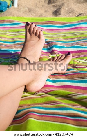 white woman feet with varnished toenails on striped towel