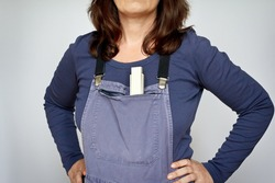 White woman in blue bip trousers or dungarees with a yardstick, arms akimbo, light background