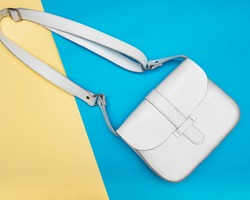 White woman leather hand bag with long handle on blue and yellow background. Flat lay
