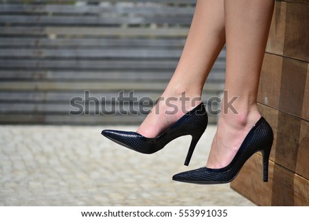 White woman wearing a black pair of high heels shoes #553991035