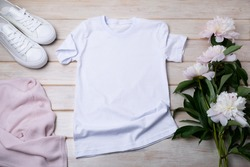 White women's cotton T-shirt mockup with pink jumper, sport shoes and tender peonies. Design t shirt template, tee print presentation mock up