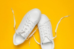 White women's leather sneakers on yellow background top view flat lay. Stylish youth sneakers, sports shoes, genuine leather footwear. Minimalistic shoe store advertising fashion style Shoe background