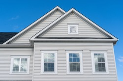 White wood accents along roof lines and above windows with using vinyl boards triangle gable covered by horizontal vinyl siding, fascia and an attic white window frame