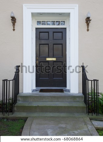 White wood bordered black door of beige stucco house