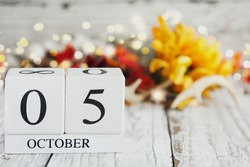 White wood calendar blocks with the date October 5th and autumn decorations over a wooden table. Selective focus with blurred background. World Teachers' Day.