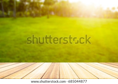 white wood floor overlook the green lawn blurs with golden light at sunset for the background.. Services include product display  template #685044877