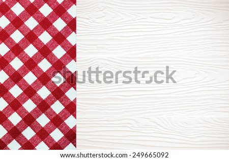 White wood table covered with red checked tablecloth, top view, background, product display template