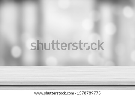 White wood tabletop over blur white bokeh light background. Empty wood shelf for product display, banner or mockup.