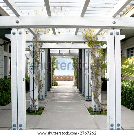 White Wooden Arbor/Pergola with blue sky in distance.