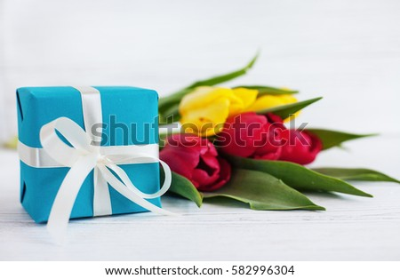 White wooden background, tulips and blue gift. Concept of holiday, birthday, Easter, March 8.