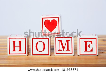 white wooden blocks spelling home in red