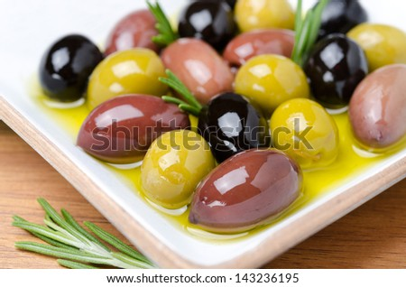 white wooden bowl with a variety of olives and rosemary in oil, selective focus