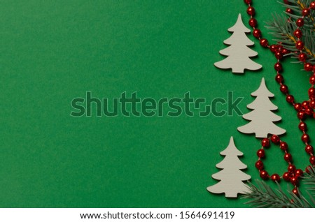 White wooden Christmas tree on a green background with red beads. New Year decoration. Copy space with copy space for your text