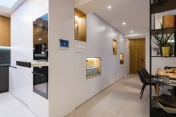 White wooden closet with with built-in appliances and shelves. Interior of modern house