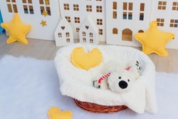 White wooden decorative houses on blue wall background. Toy houses in Christmas decor. The interior of the children's room. Paper garland in the form of stars. Soft toy white bear in a wicker basket.