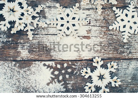 White Wooden Decorative Snowflakes on Old Vintage Background, as the Christmas Decor. Tinted photo