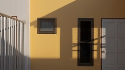 White wooden door and storage compartment with sunlight and shadow on yellow house building wall