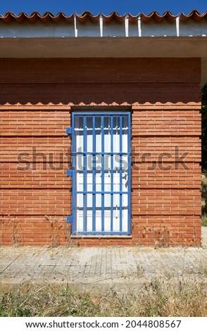 white wooden door protected by blue metal grid door in a red brick wall Zdjęcia stock ©