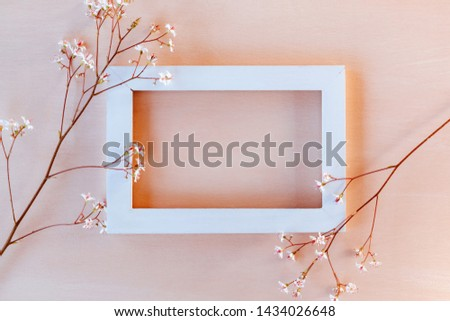 White wooden frame on a coral textured background with small flowers - a template for a greeting card or invitation