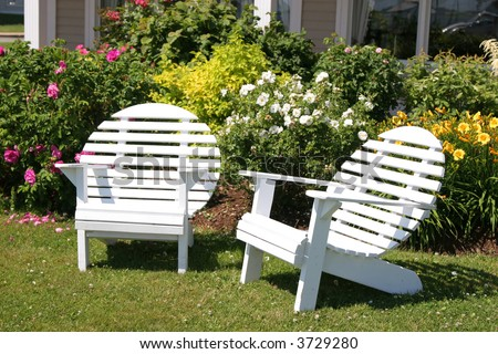White wooden lawn chairs with a circular back. - stock photo
