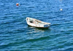 White wooden old rowboat floating on the sea moored at famous Rias Baixas in Galicia Region. Spain.