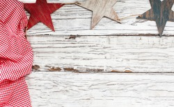 White wooden picnic table with crumpled red and white gingham tablecloth and wood stars. Free space for text.