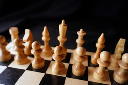 White wooden pieces on a chessboard. A chessboard set up during a game on a black background.