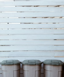 White wooden planks background with three plastic garbage trash bins down, environmental backdrop