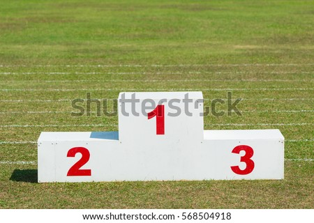 white wooden sport award stand with red numbers, outdoor in the sport field on a sunny day #568504918