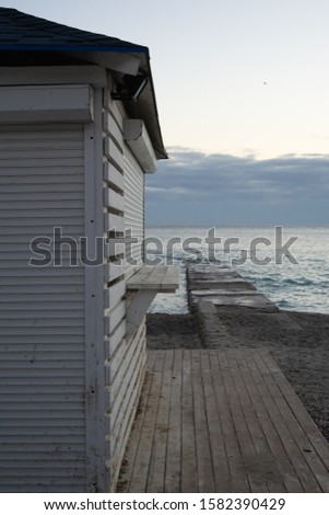 White wooden structure on the sea beach and pier. An early cloudy morning. #1582390429