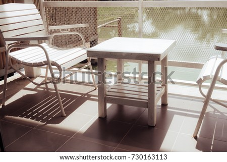 White wooden table and chairs are located on terrace of house and lake view with white steel fence and sun shining in morning. Balcony seating for relaxation in vintage tone.