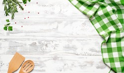 White wooden table covered with green tablecloth and cooking utensils. View from top. Empty tablecloth for product montage. Free space for your text