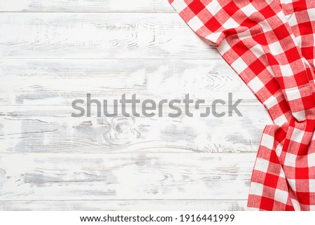 White wooden table covered with red tablecloth. View from top. Empty tablecloth for product montage. Free space for your text Stockfoto ©